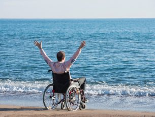 Disabled young man sitting on wheelchair on the beach with his arms wide open